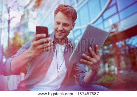 Low angle view of business executive using mobile phone and digital tablet outside office