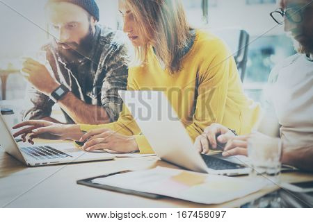 Young team of coworkers working together in modern coworking office.Bearded man talking with colleague about new startup project.Business people brainstorm concept.Horizontal, blurred
