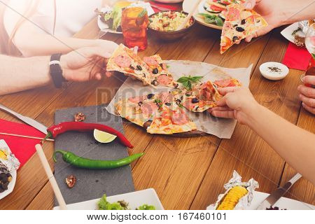 People eat pizza together at festive table served for party. Friends celebrate with catering food on wooden table closeup. Woman and man's hands take the pieces of italian pizza.