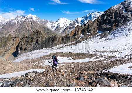 Young female climber with a backpack on his back climbs up the using trekking poles. Against the background of the high snow-capped mountains and glacier