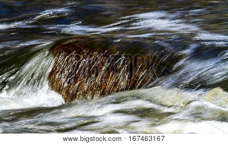 Water flowing over a rock in a mountain creek