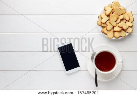 Breakfast of cup of tea and homemade heart shaped cookies and smartphone on wooden table. Morning reading news feed on the phone. Top view copy space.