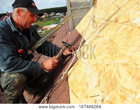 KIEV UKRAINE - February 13 2017: Roofing Contractor. Roofing Construction and Building New House with Modular Chimney Exterior. Roofer Install Repair Asphalt Shingles or Bitumen Tiles on the Rooftop Outdoor