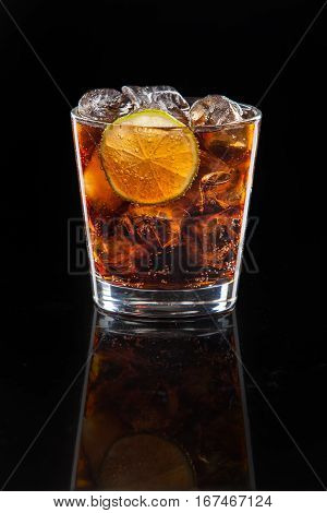 a cocktail of Cola with ice and lime on a black background