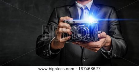 Businessman taking photo with vintage camera . Mixed media