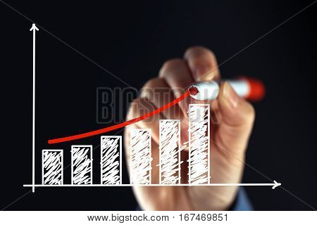 Businesswoman drawing rising graph with red marker pen