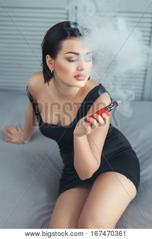 Woman sexy smoke in the room sitting on the bed.