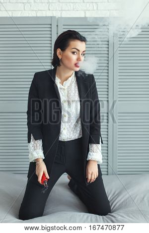 Woman with electric cigarette it is in a business suit.