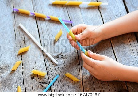 Development of fine motor skills for kids. Small kid holds a straw and a raw pasta in his hands. Creative kids activity. Easy exercise to improve hand and eye coordination. Wooden background