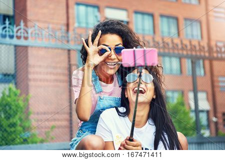 Laughing Woman With Friend Making Ok Symbol