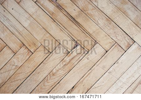 Close top view on rich texture of old brushed and distressed wooden parquet floor made from many racks in herringbone pattern, abstract background image