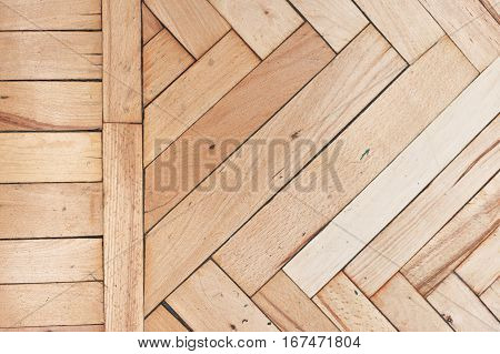 Close top view on rich texture of old brushed and distressed wooden parquet floor made from many racks in herringbone and simple row pattern on side, abstract background image