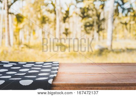 table covered with tablecloth with nature background empty wooden table for product display