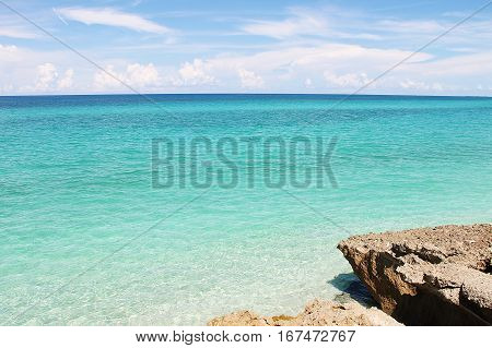 Seascape - bright azure Caribbean Sea, cumulus clouds and rocky. Picture taken in Cuba.
