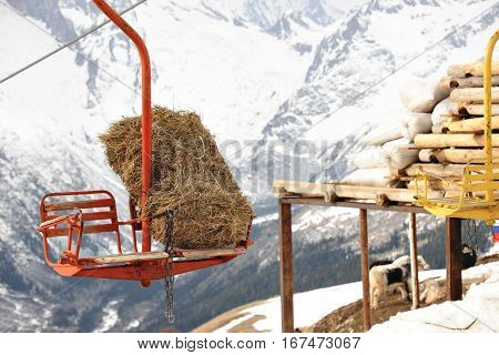 Old grunge and rust skilift with double chair used as transport for a bale of hay from downtown to ski slope for sheppards to feed animals.