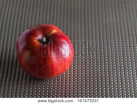 Red Apple on a gray substrate material close-up