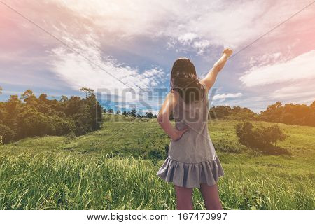 Woman standing in the field celebrate victory sign. Healthy environment victory. Business and work success concept.