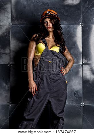 sexy female miner worker with pickaxe, in coveralls over his naked body.