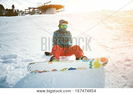 Fully equipped and covered from cold beginner girl snowboarder wears her google mask, sits alone at top of ski slope near ski lift in sun rays, ready to stand up and ride down
