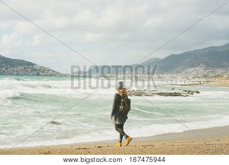 Young woman traveler in grey coat with backpack walking on sandy beach and looking at stormy Mediterranean sea in winter, Alanya, Turlkey