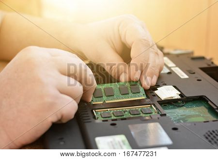 Engineer restores the laptop PC. Installing the hard drive hardware, RAM. Cleaning the notebook. Electronic repair shop, technology renovation, business, concept repairs.