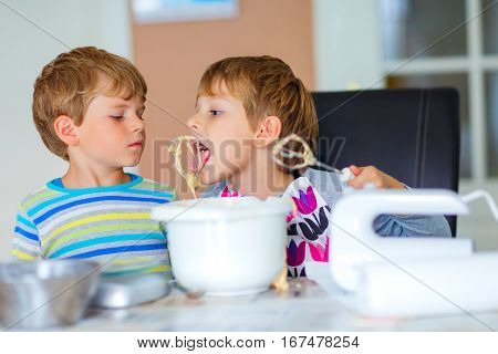 Two little funny twins brothers baking apple cake in domestic kitchen. Kid boys having fun with working with mixer, eggs and honey. Children tasting dough