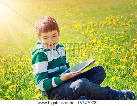 Happy child sitting on the field with dandelions holding tablet. Boy laughing on sunny day in springtime