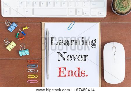 Text Learning never ends on white paper which has keyboard mouse pen and office equipment on wood background / business concept.