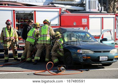 Sunset Beach, California - JANUARY 27, 2017: Sunset Beach- Fire Rescue use their Extrication tools aka the JAWS of LIFE cut and remove doors to remove injured and transport them to Hospital.