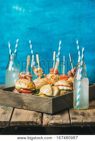 Home party food concept. Homemade burgers with sticks in wooden tray and lemonade in bottles with straws on rustic shabby table, bright blue painted wall at backgound, selective focus, copy space