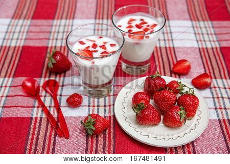 Two Glasses of Yogurt,Red Fresh Strawberries are in the Ceramic Plate with Plastic Spoons on the Check Tablecloth.Breakfast Organic Healthy Tasty Food.Cooking Vitamins Ingredients.Summer Fruits.