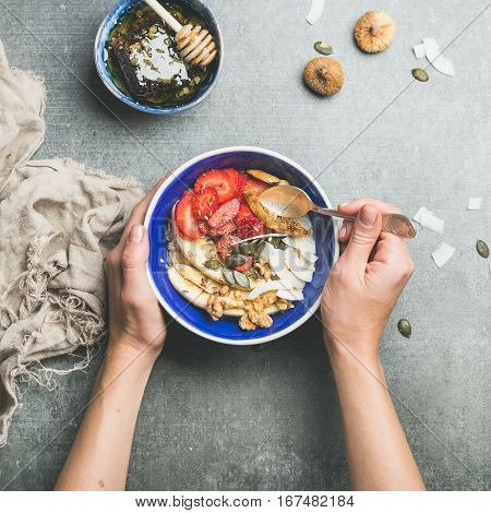 Yogurt, granola, seeds, fresh and dry fruit and honey in blue ceramic bowl in woman' s hands over grey concrete background, top view, square crop. Clean eating, detox, dieting, vegetarian food concept