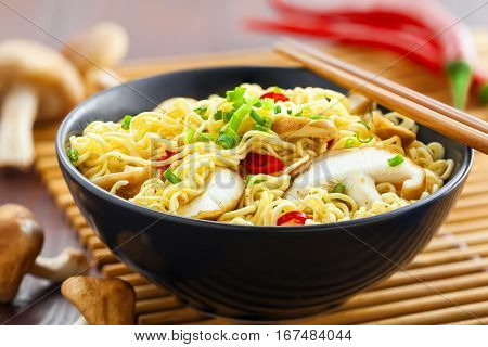 Bowl of instant noodles with shiitake mushrooms pepper and onion on table Asian food