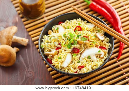 Instant noodles with shiitake mushrooms pepper and onion in a bowl Asian meal on a table top view