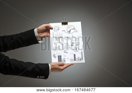 Male hands holding business plan on blank on dark background and showing it