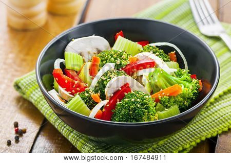 Steamed broccoli with onion mushroom carrot and pepper. Vegetable salad in bowl. International healthy vegetarian food.