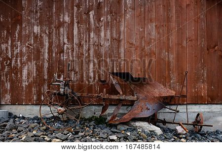 Old times farming tool rusting in front of a wooden barn. The heavy metal plow is rusty and weathered. In the past it was used to work on the field, pulled by a strong animal like a horse, an ox or a mule.