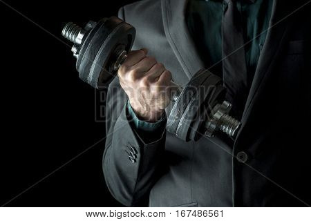 Businessman in formal suit lifting weights. Concept of power and determination in business. Over black background.
