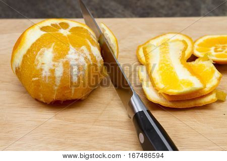 An orange being peeled An orange being peeled on  a wooden chopping board