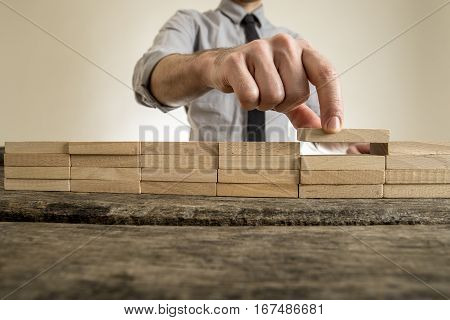 Fingers placing wooden block on orderly stack with unidentifiable man in necktie in background.