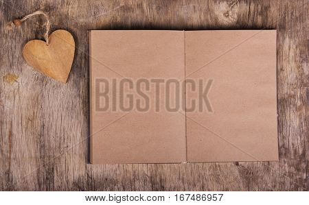 Open book with blank pages and a valentine from a tree. Notebook made from recycled paper and Valentine on the old wooden background. Valentine's Day. Copy space