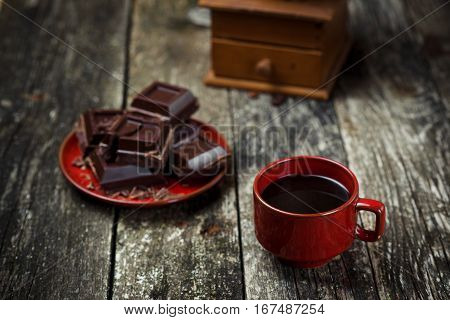 Coffee red cup, pieces of chocolate on the wooden table background. Tinted. Selective focus.