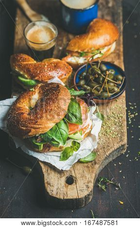 Breakfast with bagels with salmon, avocado, cream-cheese, basil, espresso coffee in glass, capers on rustic wooden board over dark scorched background, selective focus. Healthy or diet food concept