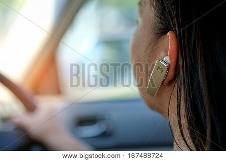 Women using hands-free phone while driving a car.