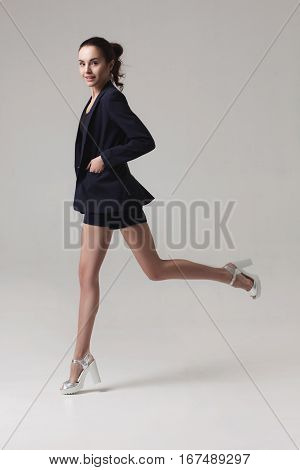beautiful fashionable brunette woman in blue jacket andsilver shoes on grey studio background. fashion motion shoot