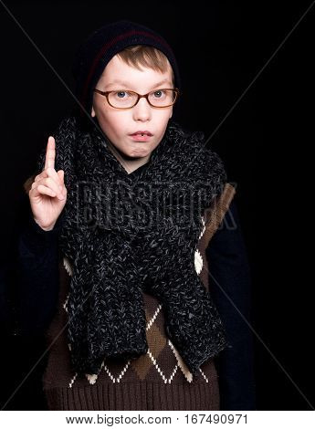 small boy or cute nerd kid in glasses hat and fashionable knitted scarf on black background holds raised finger