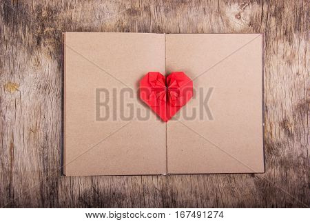 Open notebook with blank pages and Valentine origami. Red origami heart on a clean page. Copy space