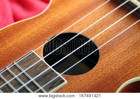 Small Hawaiian four stringed ukulele guitar closeup. Musical instruments shop or learning school concept