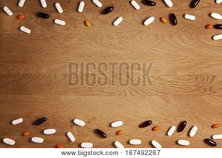 Vitamins, supplements, drugs, tablets pils on wooden table. Pharmacy, medicine and health concept. Top view. Copy space for text