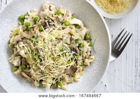 Risotto with mushrooms and peas, topped with grated parmesan.  Top view.